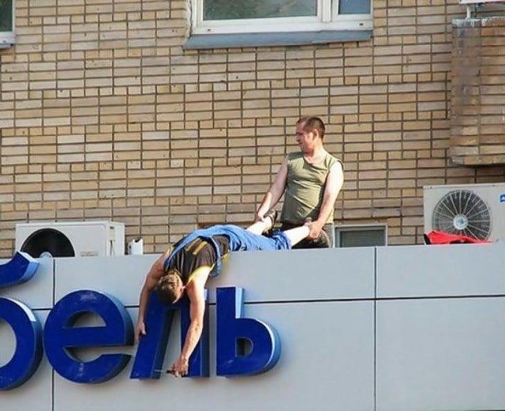 hombre deteniendo al otro de los pies para que arreglen las letras
