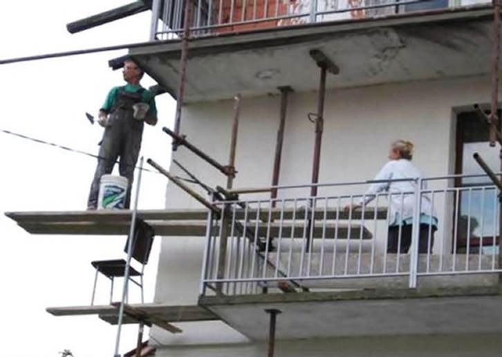 pareja pintando la casa de forma peligrosa