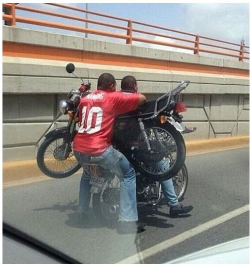 hombres en una solo moto cargan a otra moto