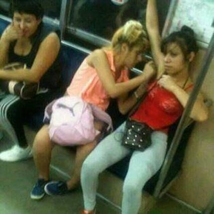 mujerdepilando a otra en el metro tiene los brazos levantados