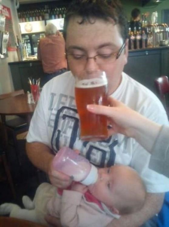 amigos le dan cerveza a papa primerizo mientras le da de comer a la bebe