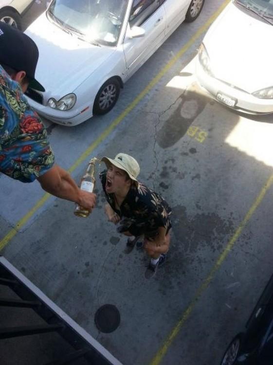 amigo dandole vino desde arriba a otro qu esta en el estacionamiento de un hotel