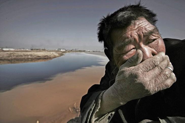 rio contaminado, anciana se cubre la nariz