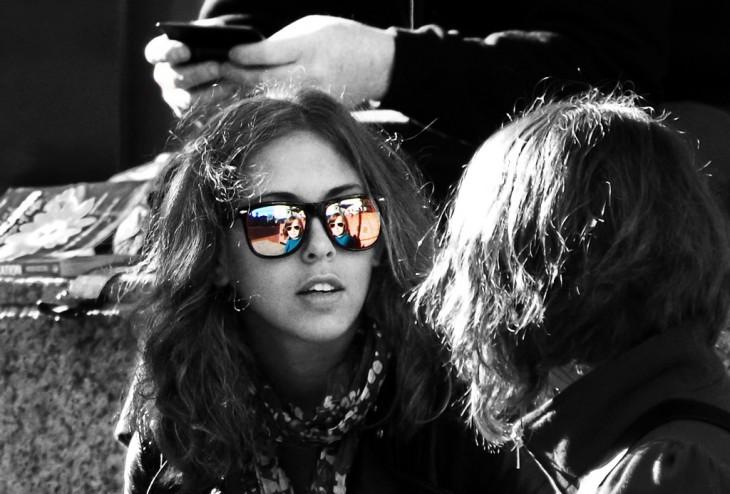 mujer en escala de grises con reflejo a color en lentes