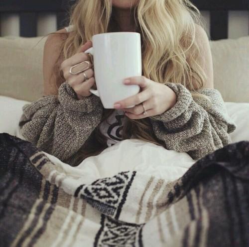 mujer tomando café cobijada