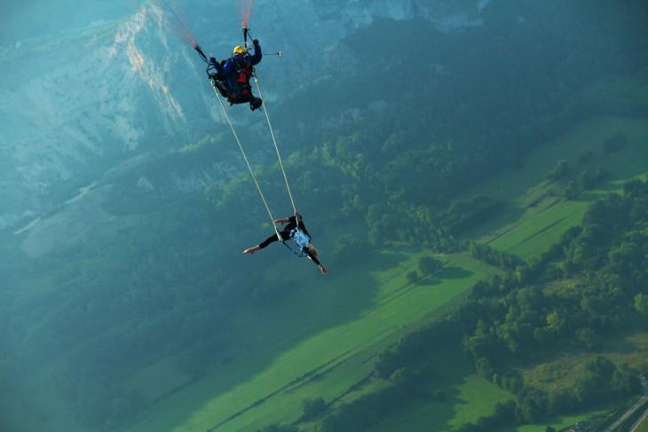 trapecista haciendo habilidades mientras baja el paracaidas