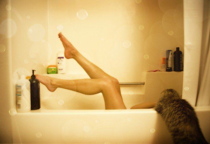 mujer en tina de baño con varios shampoos y un perro a un lado