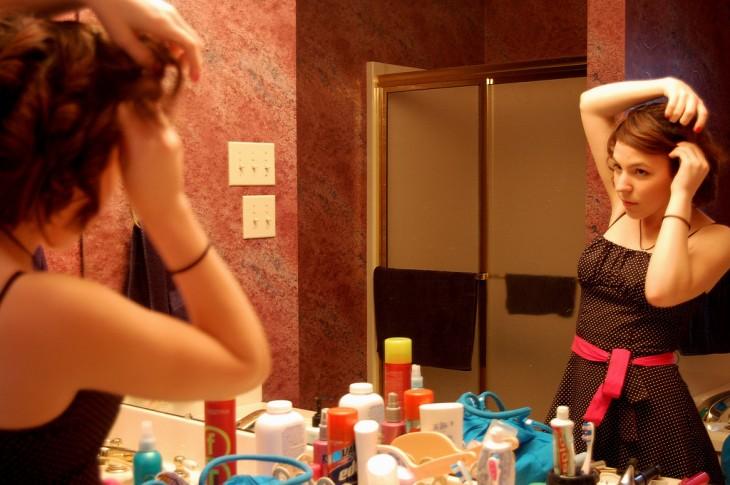 mujer peinandose con muchos productos en el baño
