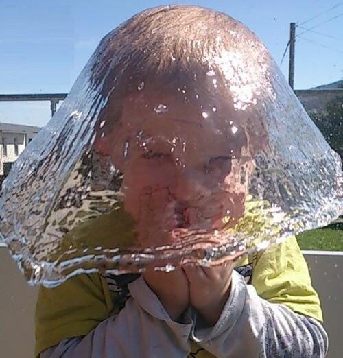 niño al que le va a caer agua que simula un gorrito