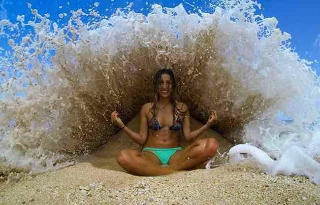 mujer haciendo Yoga justo cuando una ola le cae encima