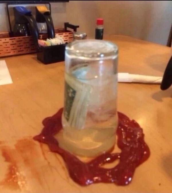 vaso invertido con agua y dentro un billete con el pago al restaurante alrededor esta con catsup