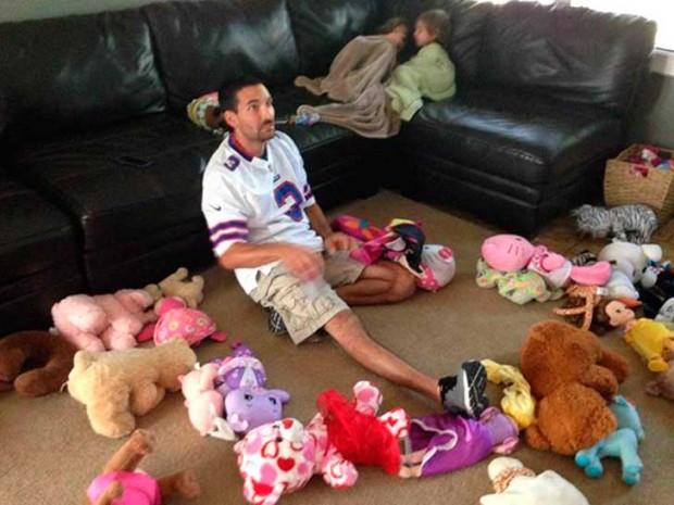 papa viendo la tele rodeado de muñecos de peluches