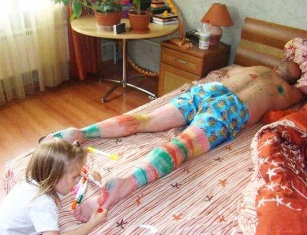 niña pintando todas las piernas a su papa mientras estadormido