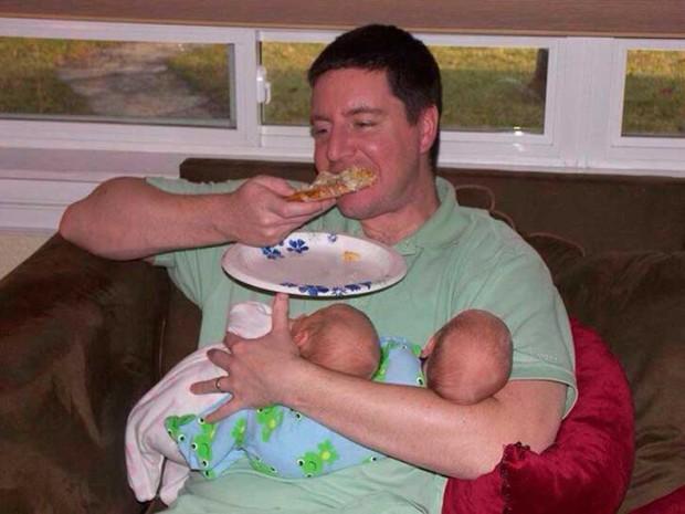 papa comiendo con sus gemelos en los brazos