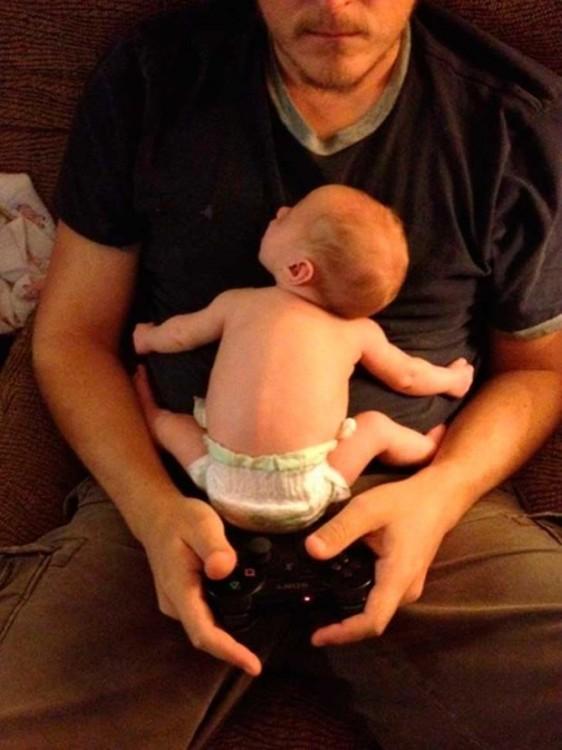 papa juega xbox con su bebe recien nacido en los brazos