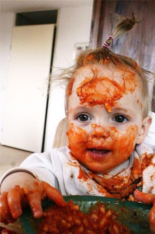bebe embarrado de papilla roja y feliz