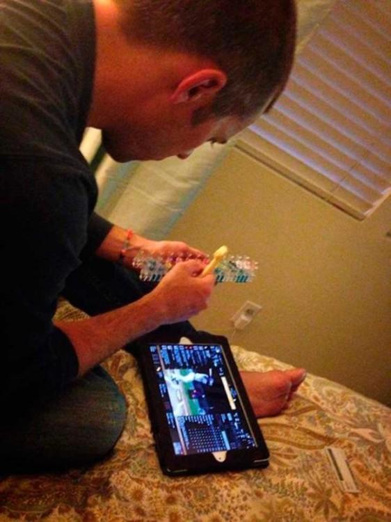 señor arregla juguete mientras ve el patrido en la tablet
