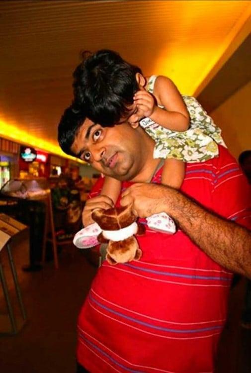 papa cargando en los hombros a su bebé dormida
