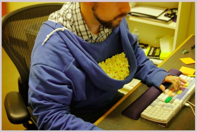 hombre con palomitas y sudadera mientras escribe en la computadora