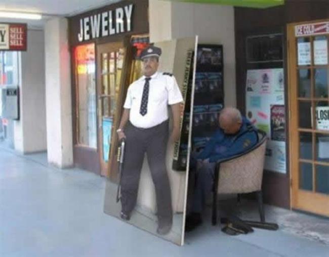 Policia dormido mientras lo cubre un poster de guardia de seguridad