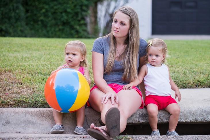 mujer sentada con sus hijas en la banqueta despues de haber jugado a la pelota