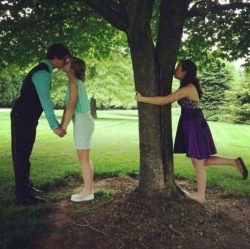 muchacha besando al un arbol y a un lado una pareja besandose