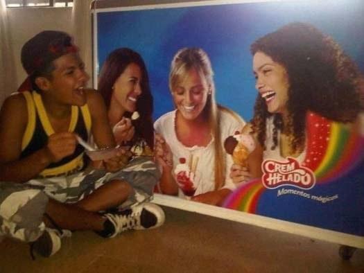 niño come un helado junto a un refrigerador con un poster de chicas riendose