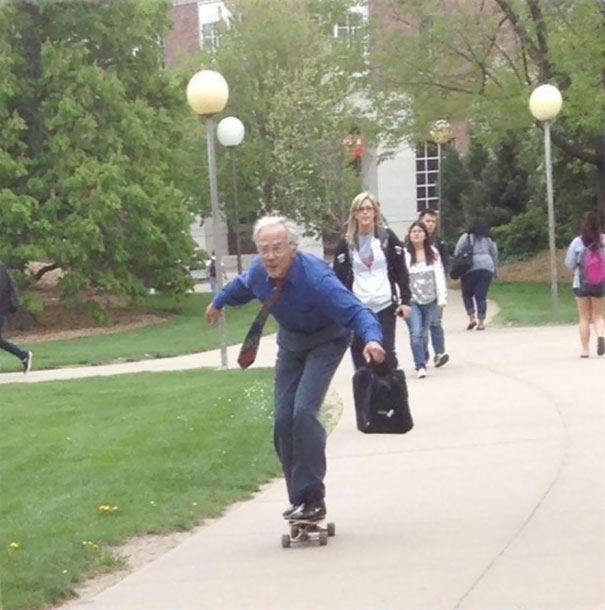 profesor de avanzada edad en patineta por la escuela para llegar a tiempo en clase
