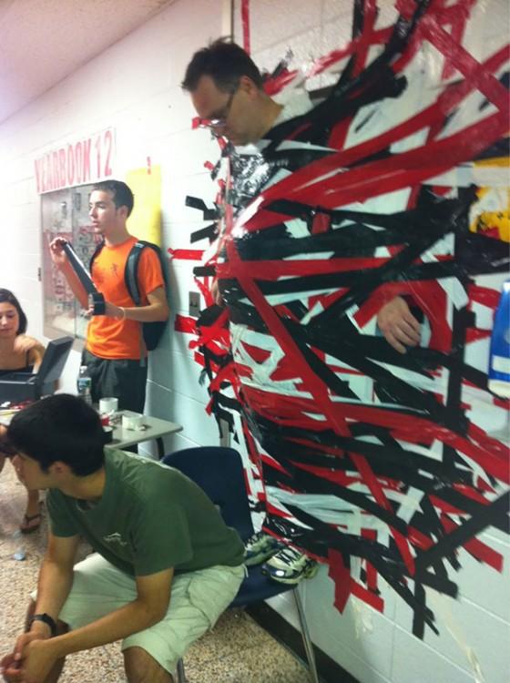 maestro pegado en la pared con cintas por sus alumnos con la finalidad de donación