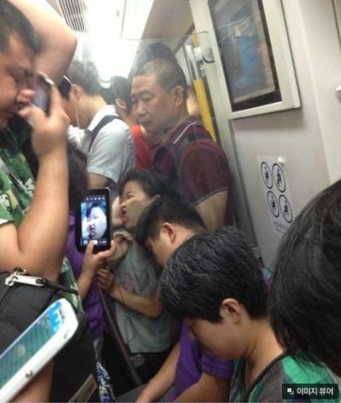 niña con la cara embarrada en el cristal mientras una señora le toma una foto en señal de asombro el papá solo las ve