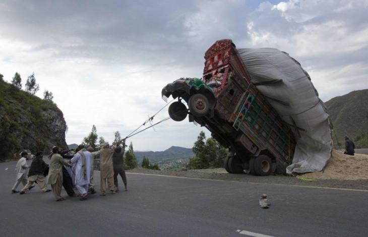 camión cargado casi cae al vacio por exceso de peso y unosseñores intentan salvarlo
