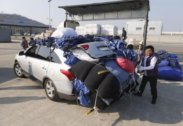 coreano amarrando pacas de ropa en su carro tipo sedan pero ya esta muy lleno