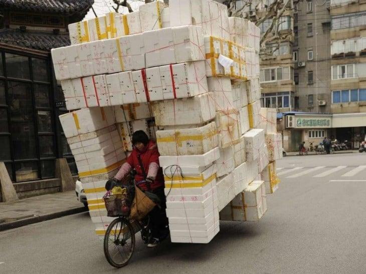 mujer cargando en la bici cajas de unicel