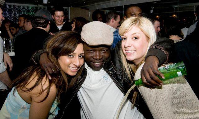 hombre tirando la cerveza por borracho posando para la foto con dos chicas que parecen cargarlo