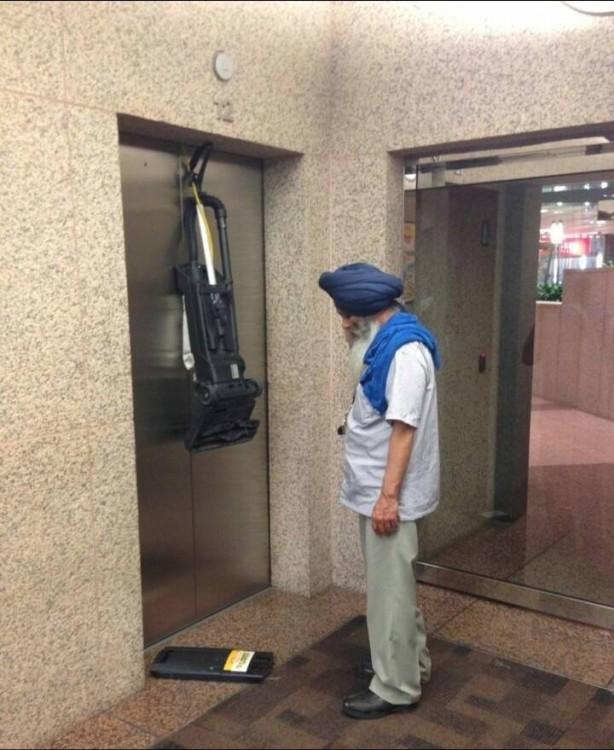 hombre de medio oriente con turbante azul viendo su aspiradora como sedestroza por dejar el cable adentro del ascensor antes de que cerrara