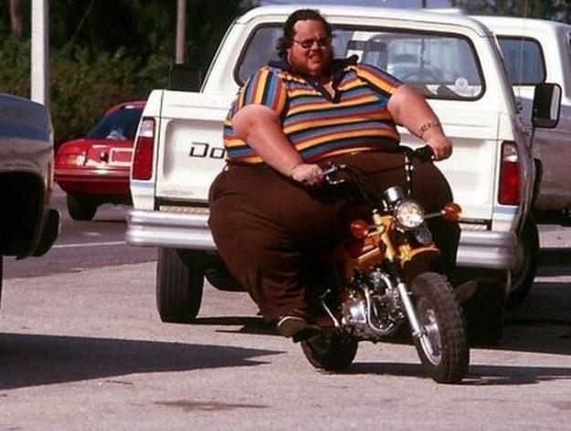 hombre con sobrepeso en una moto pequeña a él