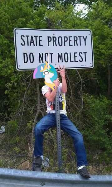 tipo con cara de unicornio colgado de un letrero donde esta prohibido hacerlo