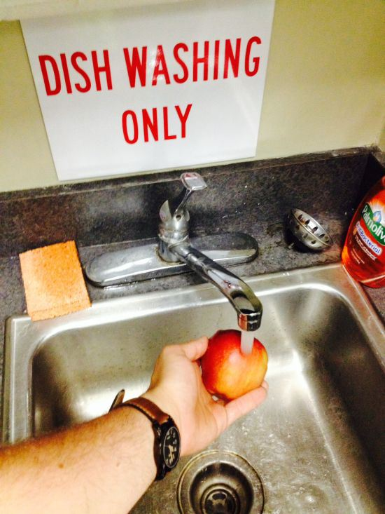 hombre lavando manzana donde solo se lavan platos