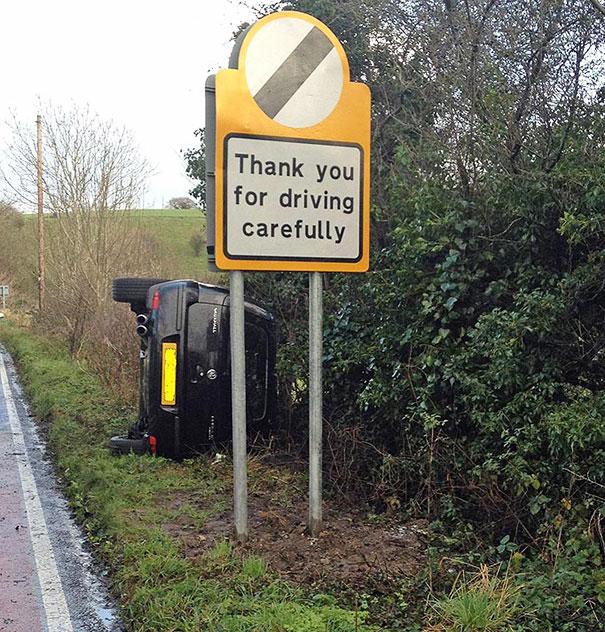auto volteado a pie de carretera delante de el, un letrero que dice gracias por manejar con cuidado