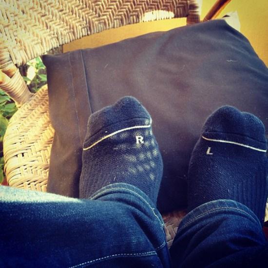pies sobre un cojin gris con calcetines puestos al reves