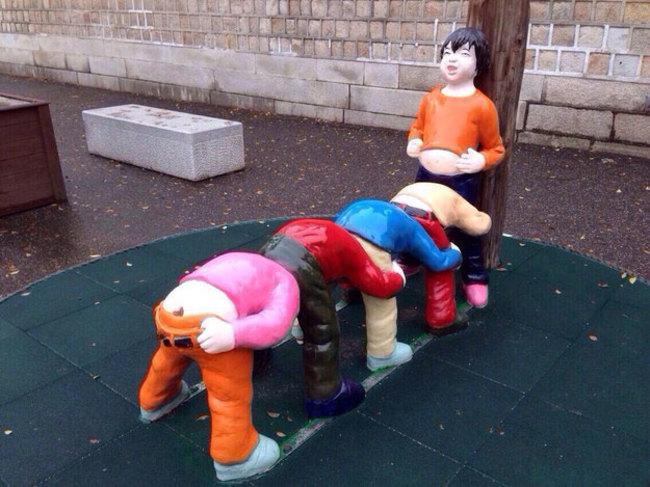 escultura de niños formados en fila  jugando