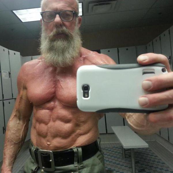 adulto mayor con un cuerpo muy trabajado se toma selfie en los vestidores del gimnasio