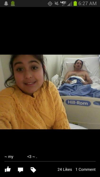 niña se toma selfie con el papa al fondo acostado en la cama de uin hospital