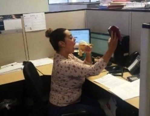 mujer se toma un selfie en la oficina mordiendo un platano