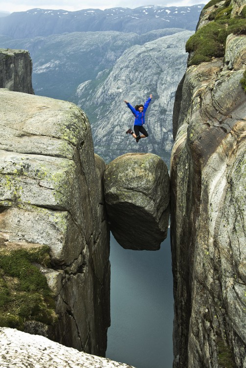 chica brincando sobre una roca en Kjeragbolten