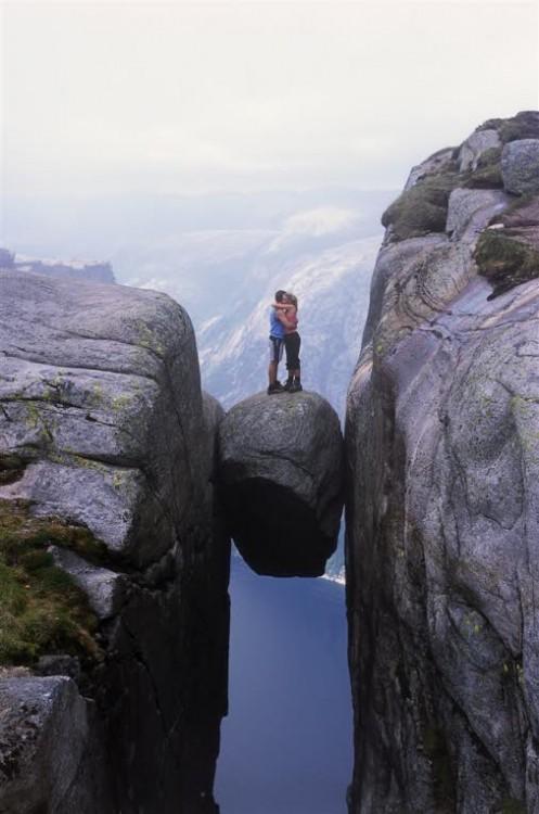 Pareja de novios abrazados sobre una roca