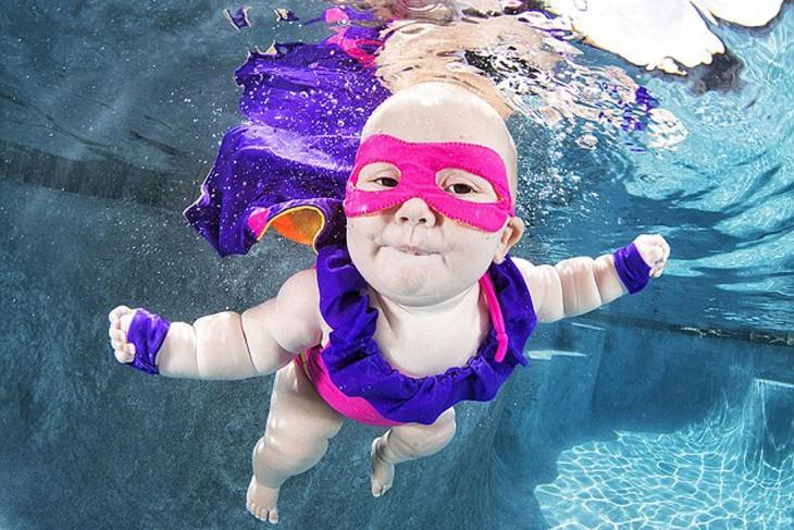 bebé super heroe  nadando bajo el agua
