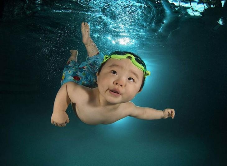 bebé chino nadando bajo el agua