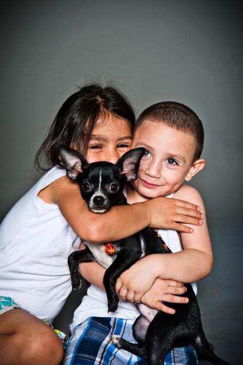 Niños abrazando a un perro chihuahua