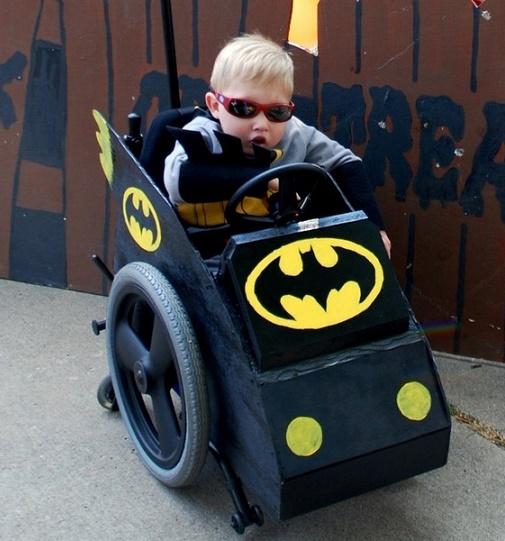 niño en su silla disfrazado de batman en su batimóvil